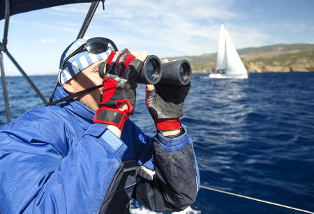 Using binoculars on a sailboat during a race